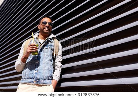 travel, tourism and lifestyle concept - smiling indian man with backpack drinking smoothie from plastic cup with straw on city street
