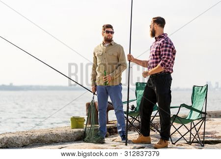 leisure and people concept - male friends with fishing rods and beer on pier at sea