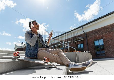 technology, leisure and people concept - indian man with smartphone, headphones and longboard listening to music on roof top