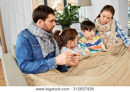 family, health and people concept - father with thermometer, mother and ill children having fever at home
