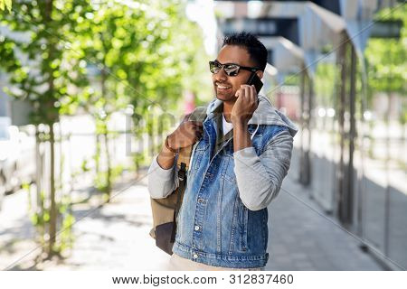 travel, tourism and lifestyle concept - smiling indian man with backpack calling on smartphone on city street