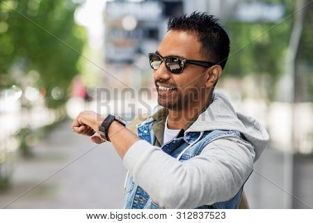 travel, tourism and lifestyle concept - smiling indian man using voice command recorder on smart watch on city street