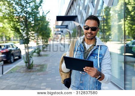 travel, tourism and lifestyle concept - smiling indian man with tablet computer and backpack on city street