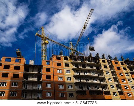 Construction Of A High-rise Building. Cranes Construction Hauling Cargo. Blue Sky