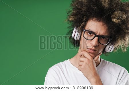 Photo closeup of brooding young man with afro hairstyle propping up his head and using headphones isolated over green background poster