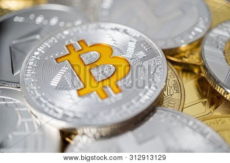 Bitcoin Physical Coin On The Stack Of Other Different Cryptocurrencies. Close-up Photo Of Bitcoin Wi