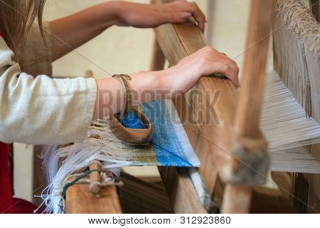 Close Up Of Woman Hands Weaving Blue And White Pattern On Loom. Traditional Weaving Technique