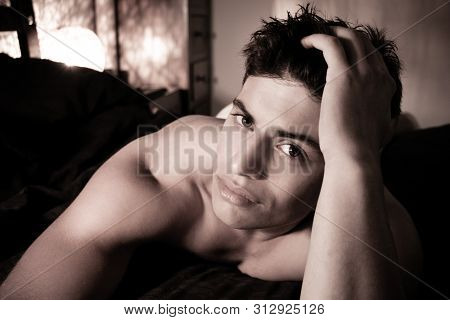 Handsome Muscular Latino Man In His Underwear Lying On Bed Looking At Camera