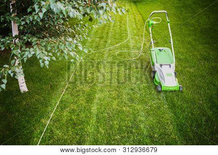 Summer work in the garden, Lawn mower in back yard