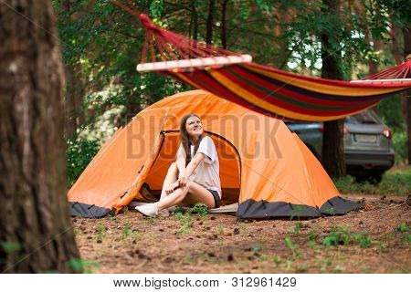 Beautiful Woman Sitting Outside Tent Enjoying Holiday Away From Bustle Of City In Forest. Lifestyle
