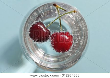 Glass Of Water And Fresh Cherries With Bubbles