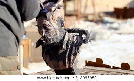 Man Holds Old Bust. Stock Footage. Man In Work Gloves Raises Dusty Old Bust Of Important Man Made Of
