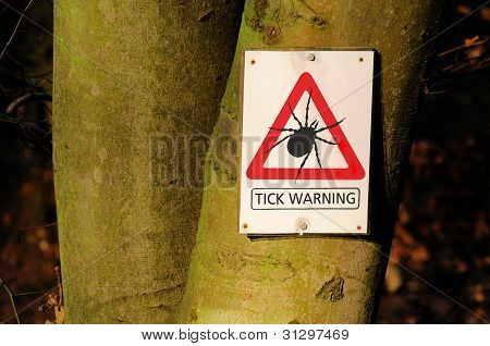 A tick warning sign at a bole poster