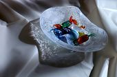 bowl of glass candy on satin poster