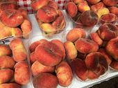 Boxes of saturn peaches sold at a market in Croatia.  The flat peach (Prunus persica var. platycarpa), also known as the doughnut peach or Saturn peach, is a variety of peach with pale yellow fruit. poster
