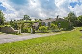 Beautiful detached house cottage in rural countryside setting with footpath and cloudy sky poster