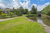 View of an English rural countryside scenery on British waterway canal with detached house during cloudy day poster