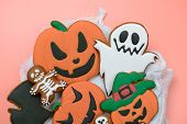The hand-made eatable gingerbread Halloween pumpkin, ghosts, bat and sceletons on pink background poster