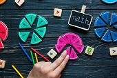 Kids hand moves colorful math fractions on dark wooden background or table. Interesting creative funny math for kids. Education, back to school concept. Geometry and mathematics materials. poster