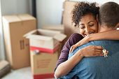 Young african woman holding home keys while hugging boyfriend in their new apartment after buying real estate. Lovely girl holding keys from new home and embracing man. Couple around cardboard boxes. t-shirt