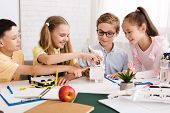 Schoolchildren with diy robot on stem education class, learning together poster