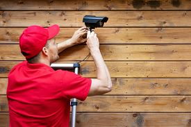 Home Security - Man Installing Outdoor Surveillance Camera On Wooden Wall Copy Space