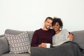 Happy multiethnic couple sitting on sofa with warm blanket. Young man and african woman embracing on couch in winter and looking at camera. Portrait of couple in love hugging on sofa with copy space.