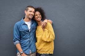 Young multiethnic couple in love isolated on grey background looking up and thinking about their future together. Smiling man and african woman hugging and looking away while planning the future.