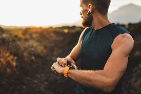 Athletic Runner Start Training On Fitness Tracker Or Smart Watch And Looking Forward On Horizon. Tra