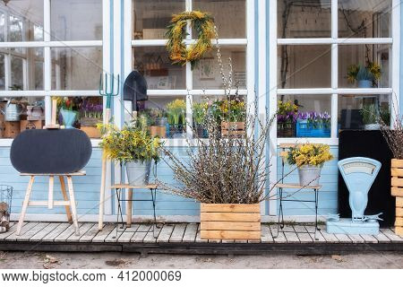 Wooden Porch Of House With Plants And Branches Yellow Mimosa. Facade Home With Garden Tools, Pots Fl