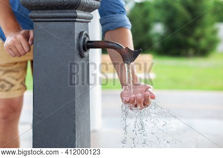 Man Washing His Hand In Faucet Water. Сity Water Tap With Drinkable Water In Park. Drinking Column.