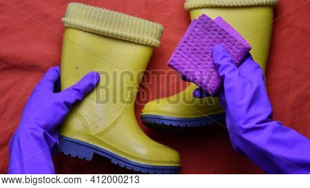 Hands In Purple Rubber Gloves Clean And Wipe Kids Yellow Boots With Wet Rag. Hands In Protective Glo