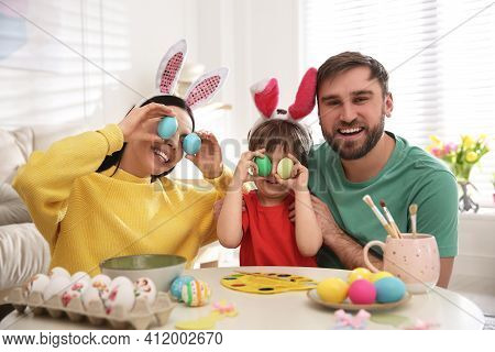 Happy Family Having Fun While Painting Easter Eggs At Table Indoors