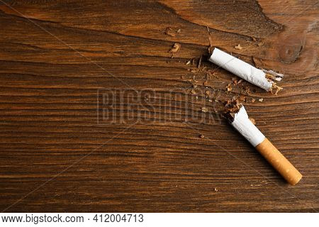 Broken Cigarette On Wooden Table, Flat Lay With Space For Text. Quitting Smoking Concept