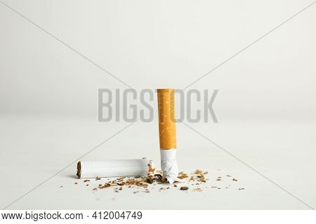 Broken Cigarette On White Table. Quitting Smoking Concept