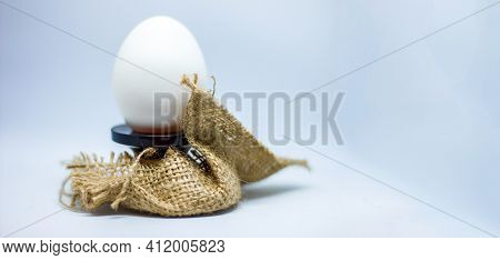 White Egg On A Stand Decorated With A Canvas In The Form Of A Nest On A Blue Background, The Theme O