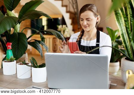 A Young Female Florist Checks Orders In The Phone App And On A Laptop, Takes Orders Online. Flower S