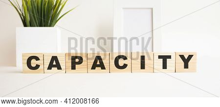 Wooden Cubes With Letters On A White Table. The Word Is Capacity. White Background With Photo Frame,