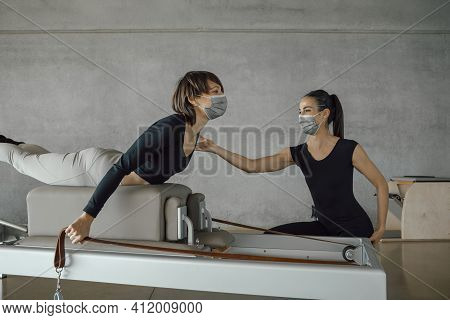 Smiling Young Woman In Face Mask And Sport Clothing, Lying Down While Practicing Pilates Exercises W