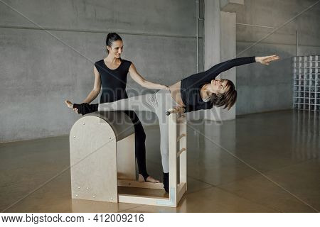 Pilates, Fitness, Sport, Training And People Concept - Full Length Woman Instructor Working Out With