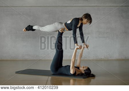 Concentrated Sporty Women Realizing A Difficult Balance Acrobat Pose, Worried For Falling. Fitness S