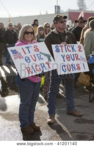 Couple Holds Signs At Rally.