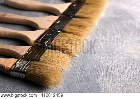 Paint Brushes On A Gray Concrete Background. Top View