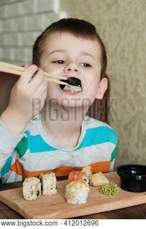 Child Eat Sushi Rolls At Home. Happy Boy Ready For Eating Sushi.