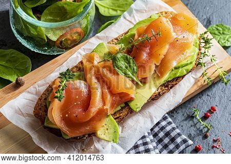 Appetizing And Healthy Smoked Salmon With Avocado And Vegetables (spinach Sprouts, Tomatoes, Thyme)