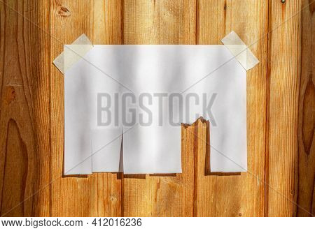 Tear off paper on wood wall. Mock up template. Street paper ad or announcement with tear-off stripes with phone number. Blank design. Copyspace mockup