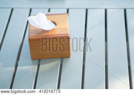 Rectangle Wooden Tissue Box And White Tissue On White Table.