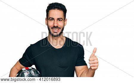 Hispanic man with beard holding motorcycle helmet smiling happy and positive, thumb up doing excellent and approval sign