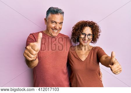 Beautiful middle age couple together wearing casual clothes approving doing positive gesture with hand, thumbs up smiling and happy for success. winner gesture.