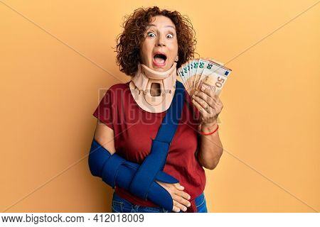 Beautiful middle age mature woman wearing cervical collar and sling holding insurance euros celebrating crazy and amazed for success with open eyes screaming excited.